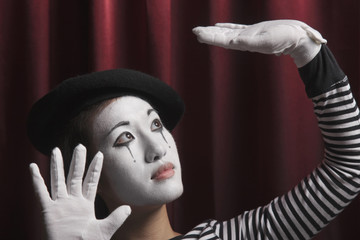 Woman in mime costume with arms raised