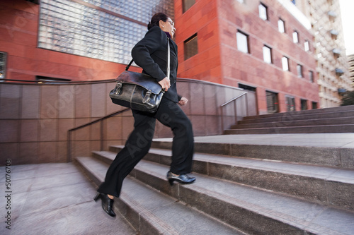Businesswoman running up steps