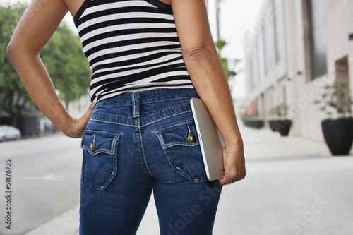 Asian woman carrying digital tablet on urban street
