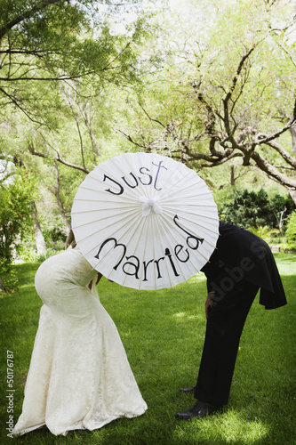Bridal couple standing behind parasol