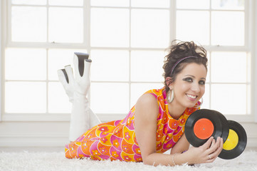 Smiling Hispanic woman in nostalgic dress holding vinyl records