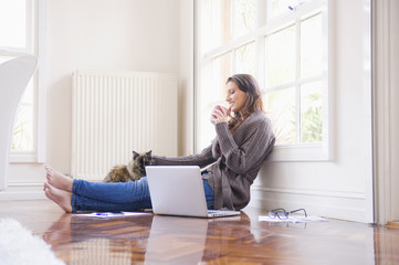 Hispanic woman sitting on floor with laptop and cat
