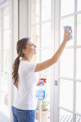 Hispanic woman washing windows