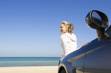 Hispanic woman leaning on car enjoying beach