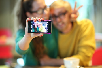 Couple taking self portrait, focus on camera
