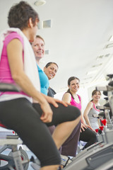 Women riding exercise bikes in health club