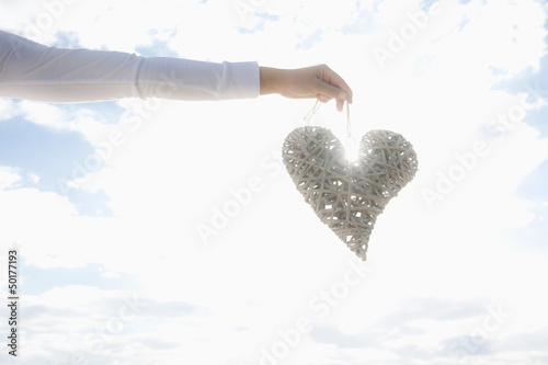 Hispanic woman holding large, woven heart