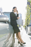 Hispanic businesswoman leaning on car and talking on cell phone