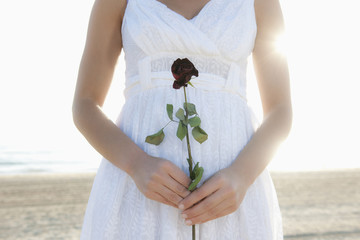 Hispanic woman holding rose on beach