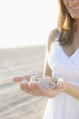 Hispanic woman holding seashells on beach