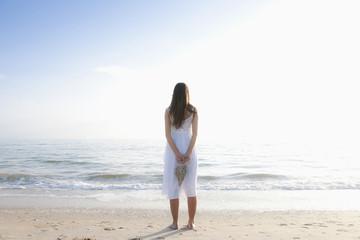 Hispanic woman holding large, woven heart on beach