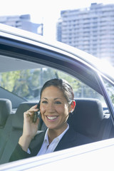 Hispanic woman talking on cell phone in back of car