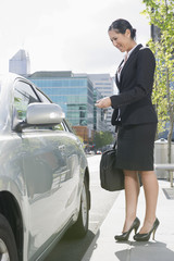 Hispanic businesswoman using keyless entry to open car door