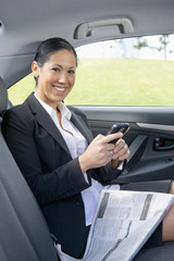 Hispanic businesswoman text messaging in back of car