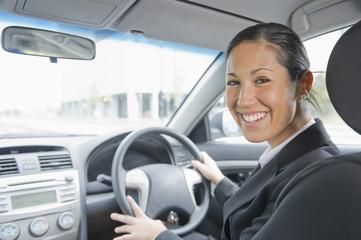 Smiling Hispanic businesswoman driving car