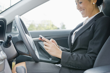 Hispanic businesswoman text messaging on cell phone in car