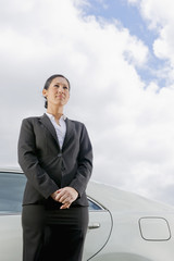 Hispanic businesswoman standing next to car