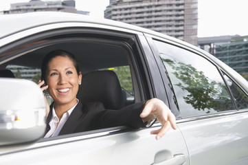 Hispanic businesswoman talking on cell phone in car