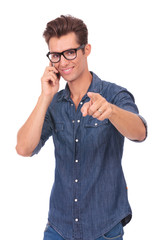 man talks on phone & points at you