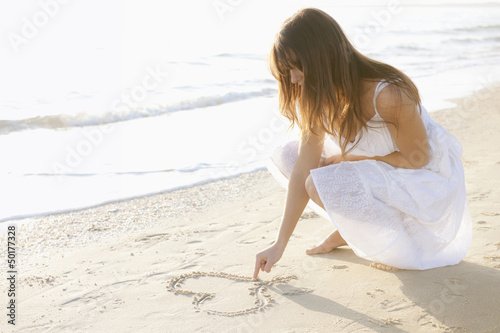 Hispanic woman drawing a heart on beach