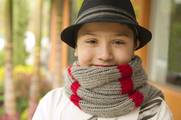 Smiling Hispanic boy in hat and scarf