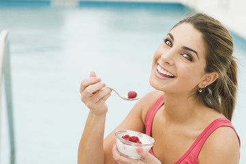 Caucasian woman eating yogurt and berries
