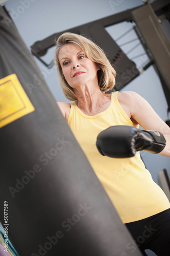Caucasian woman boxing with punching bag