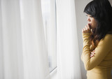 Pacific Islander woman looking out window