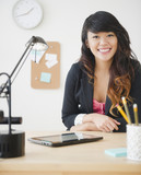 Pacific Islander businesswoman sitting at desk with digital tablet