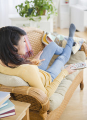 Pacific Islander woman laying on sofa watching television