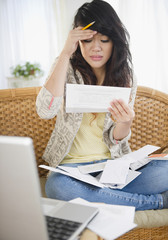 Frustrated Pacific Islander woman paying bills