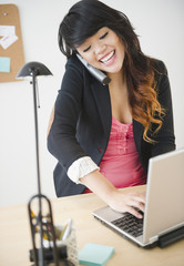 Pacific Islander businesswoman using laptop and talking on telephone