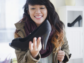 Pacific Islander woman looking at high heels in store