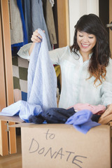 Pacific Islander woman putting donated clothing into box