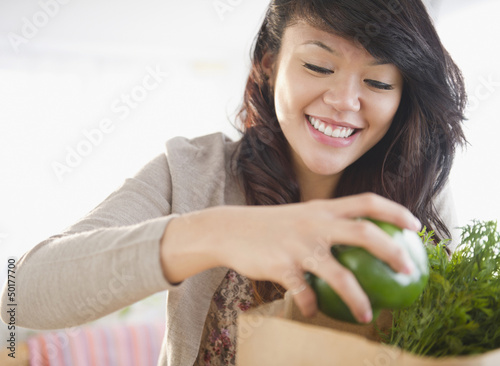Pacific Islander woman taking groceries from grocery bag