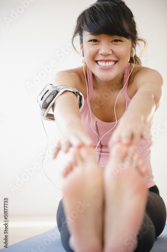 Pacific Islander woman stretching before exercise