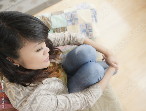 Pacific Islander woman thinking and sitting on sofa