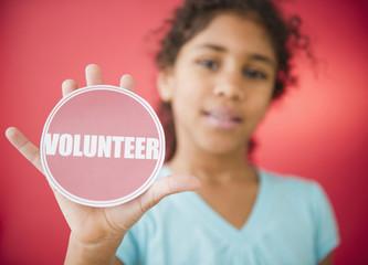 Mixed race girl holding volunteer sticker