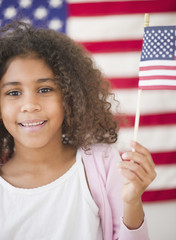 Mixed race girl holding American flag