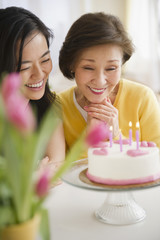 Japanese mother and daughter looking at birthday cake