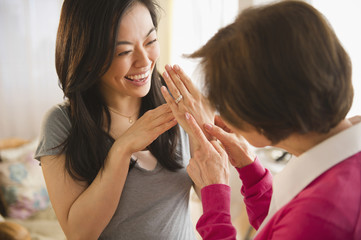 Japanese daughter showing engagement ring to mother