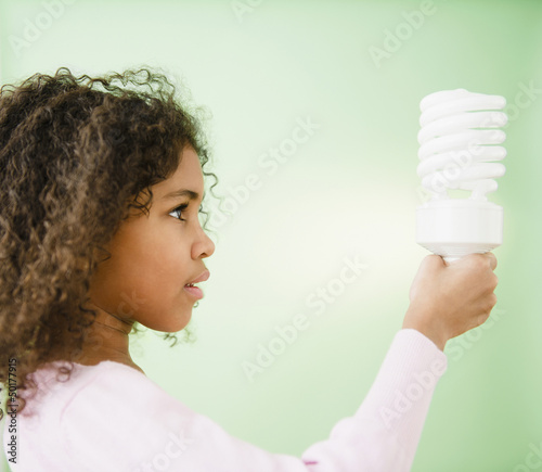 Mixed race girl holding CFL lightbulb