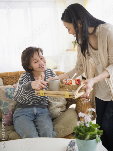 Japanese daughter bringing mother breakfast on a tray