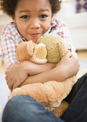 Black boy hugging teddy bear