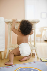 Black baby girl pulling up on table