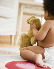 Black baby girl holding teddy bear