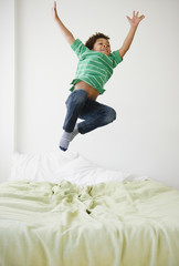 Black boy jumping on bed