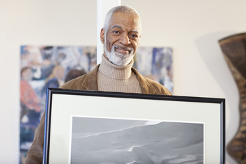 Black art gallery curator holding picture