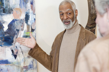 Art gallery curator showing painting to customer