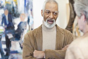 Art gallery curator talking to customer